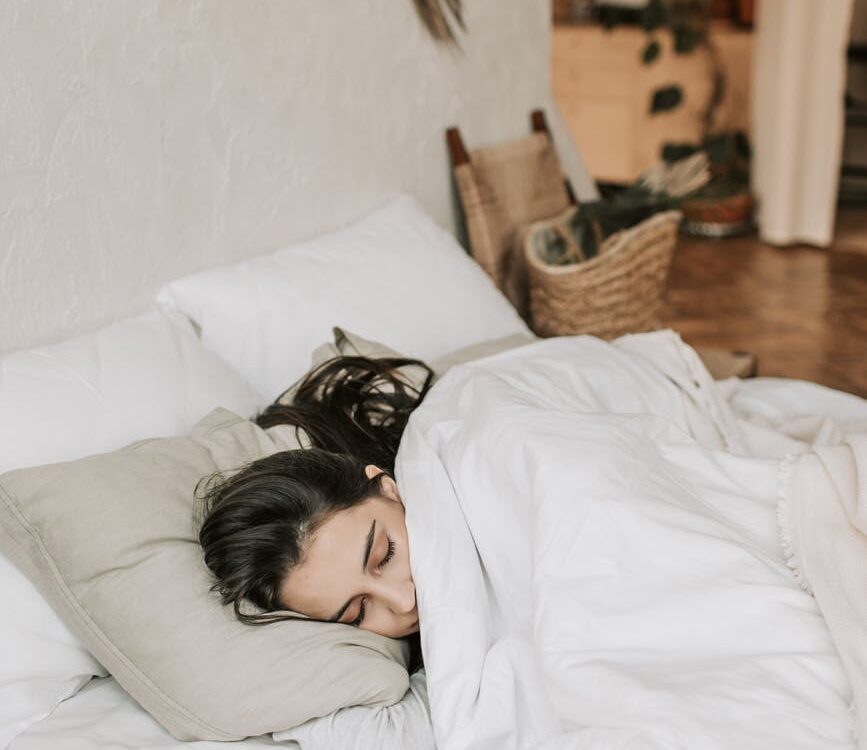 woman sleeping on a bed with white blanket